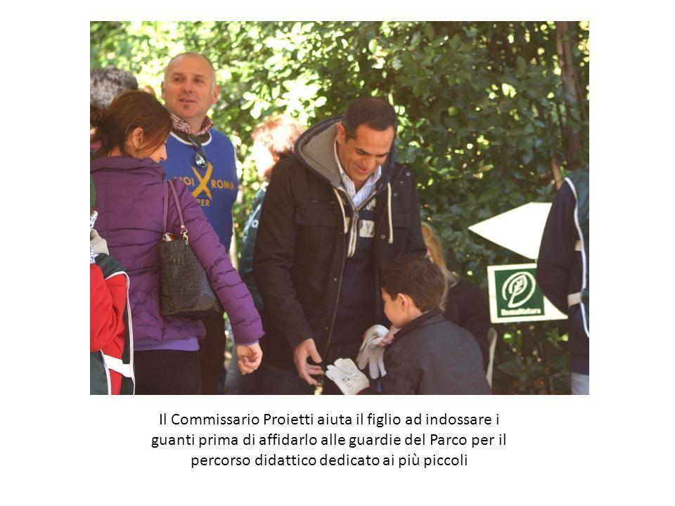 Il Commissario Proietti aiuta il figlio ad indossare i guanti prima di affidarlo alle guardie del Parco per il percorso didattico dedicato ai più piccoli