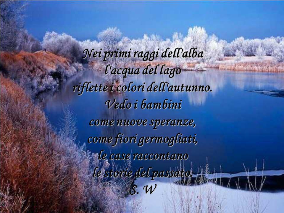 Nei primi raggi dell'alba l'acqua del lago riflette i colori dell'autunno. Vedo i bambini come nuove speranze, come fiori germogliati, le case raccont