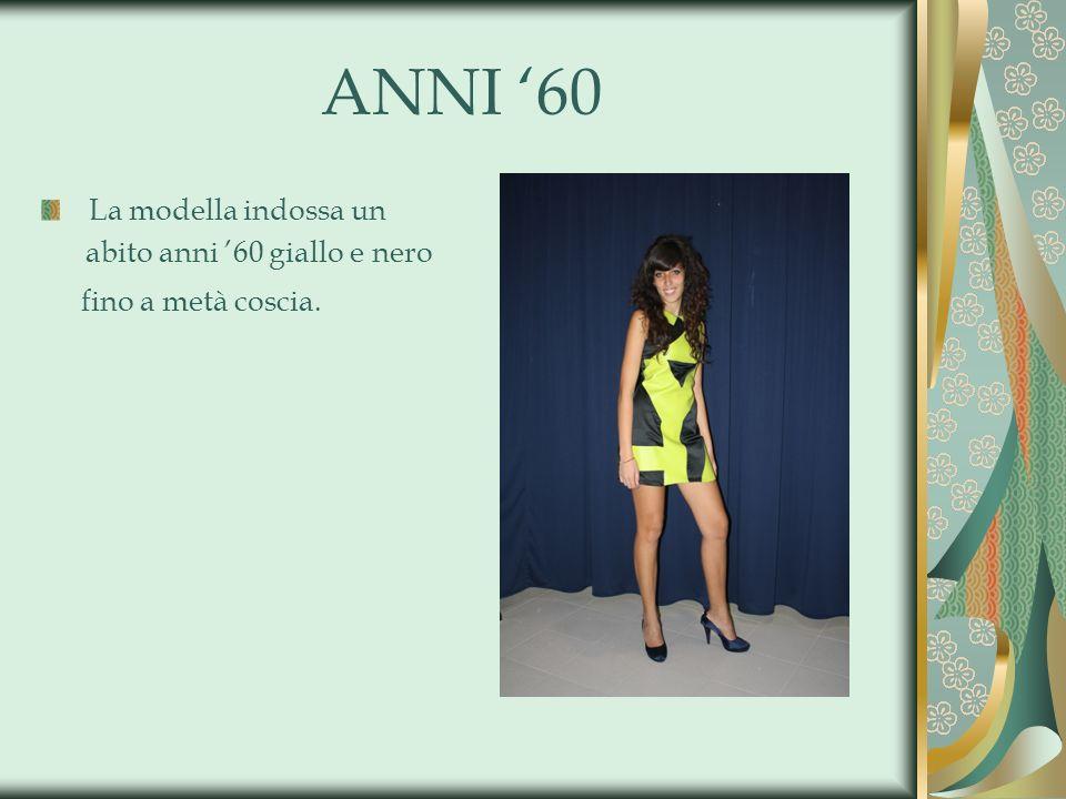 ANNI 60 La modella indossa un abito anni 60 giallo e nero fino a metà coscia.