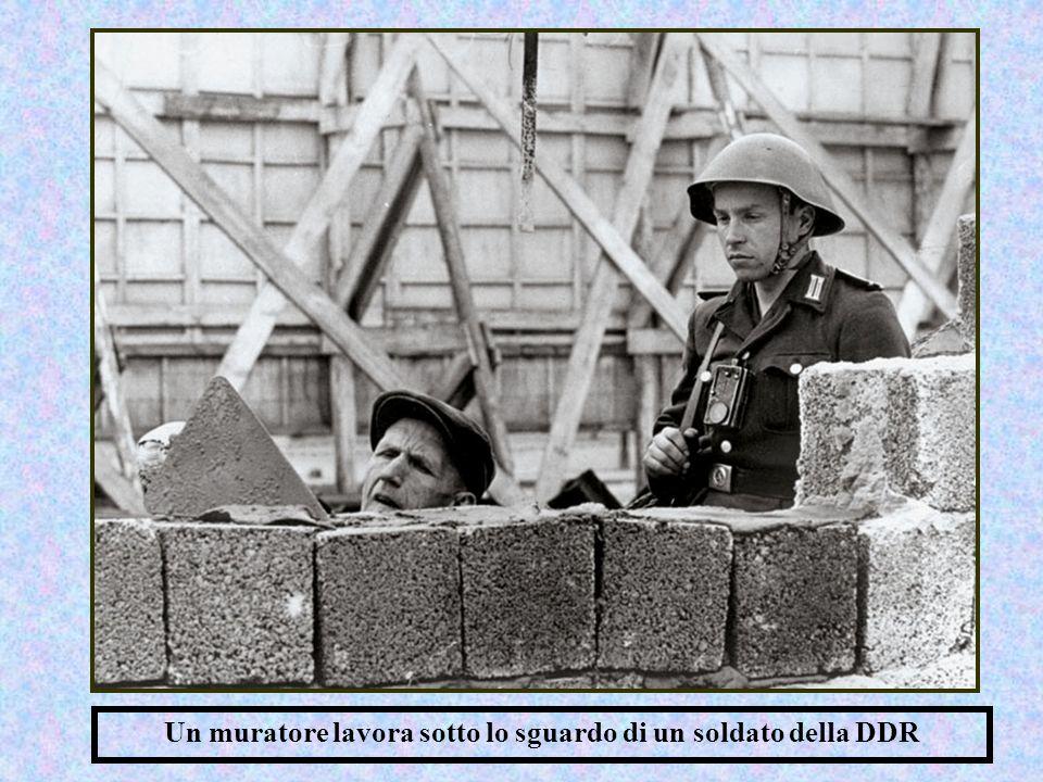 Un muratore lavora sotto lo sguardo di un soldato della DDR