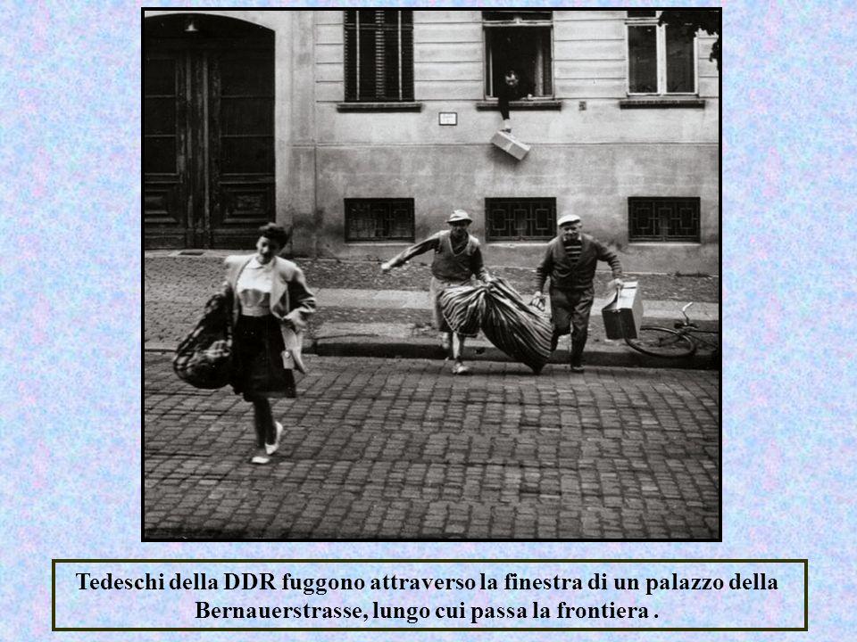 Tedeschi della DDR fuggono attraverso la finestra di un palazzo della Bernauerstrasse, lungo cui passa la frontiera.