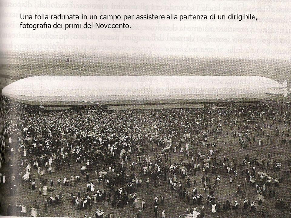 Una folla radunata in un campo per assistere alla partenza di un dirigibile, fotografia dei primi del Novecento.