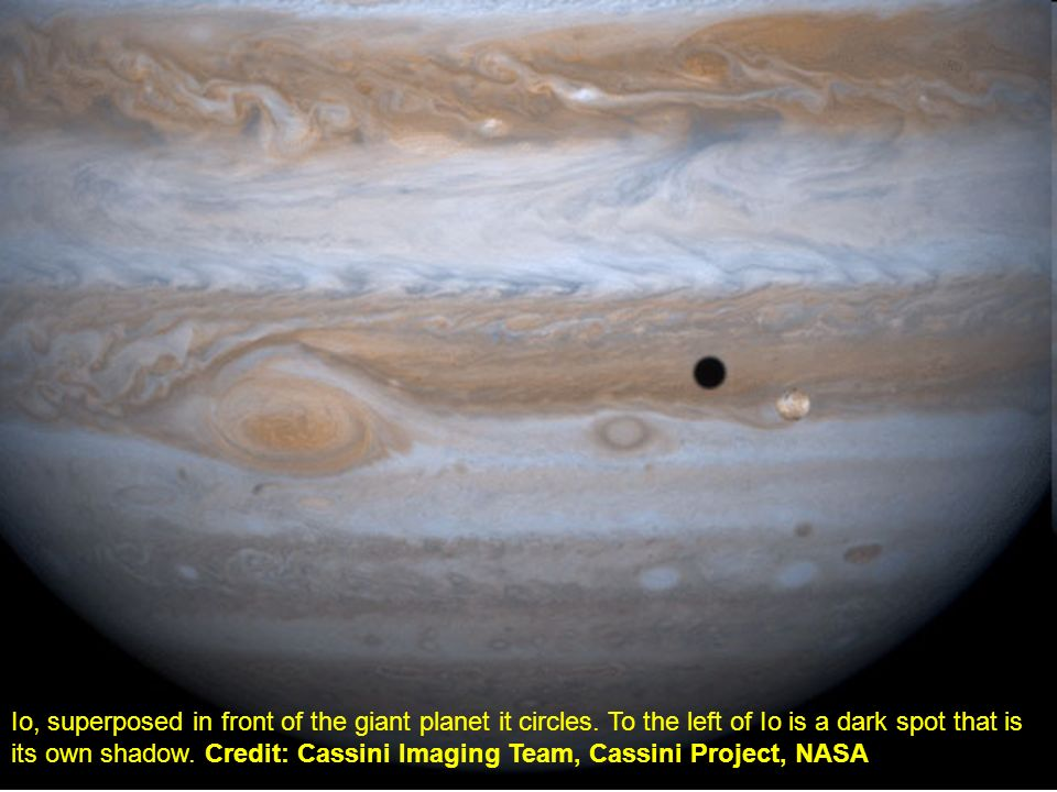 Io, superposed in front of the giant planet it circles. To the left of Io is a dark spot that is its own shadow. Credit: Cassini Imaging Team, Cassini