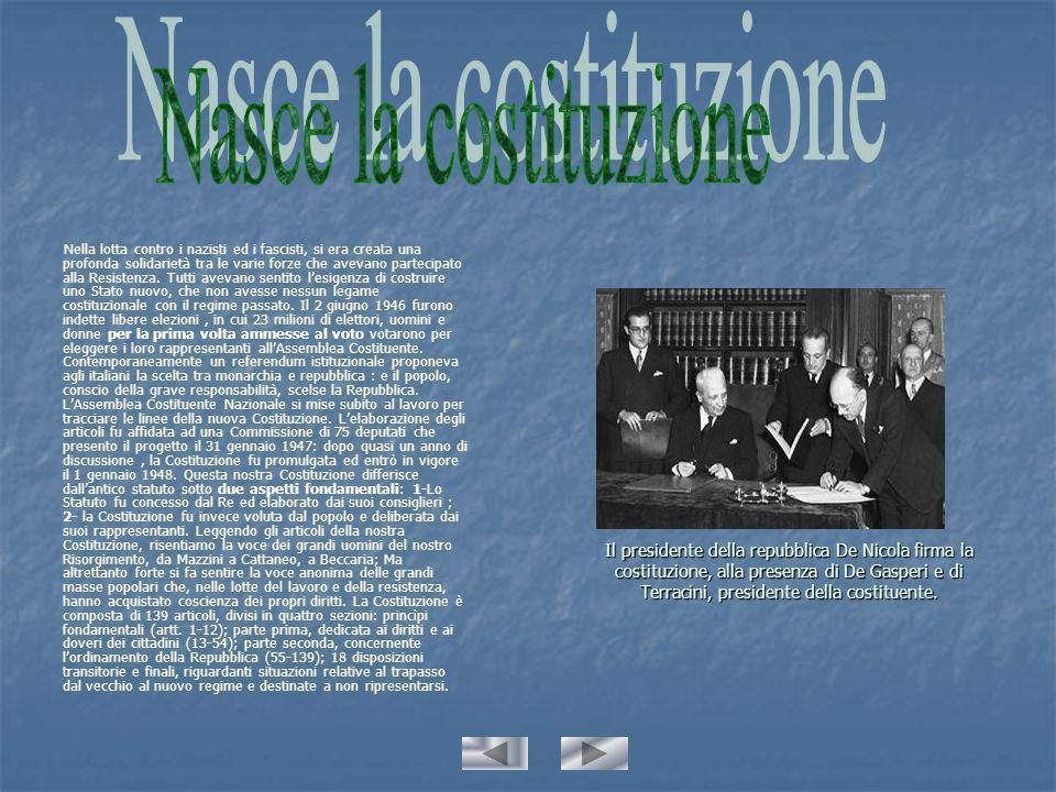 Il presidente della repubblica De Nicola firma la costituzione, alla presenza di De Gasperi e di Terracini, presidente della costituente.