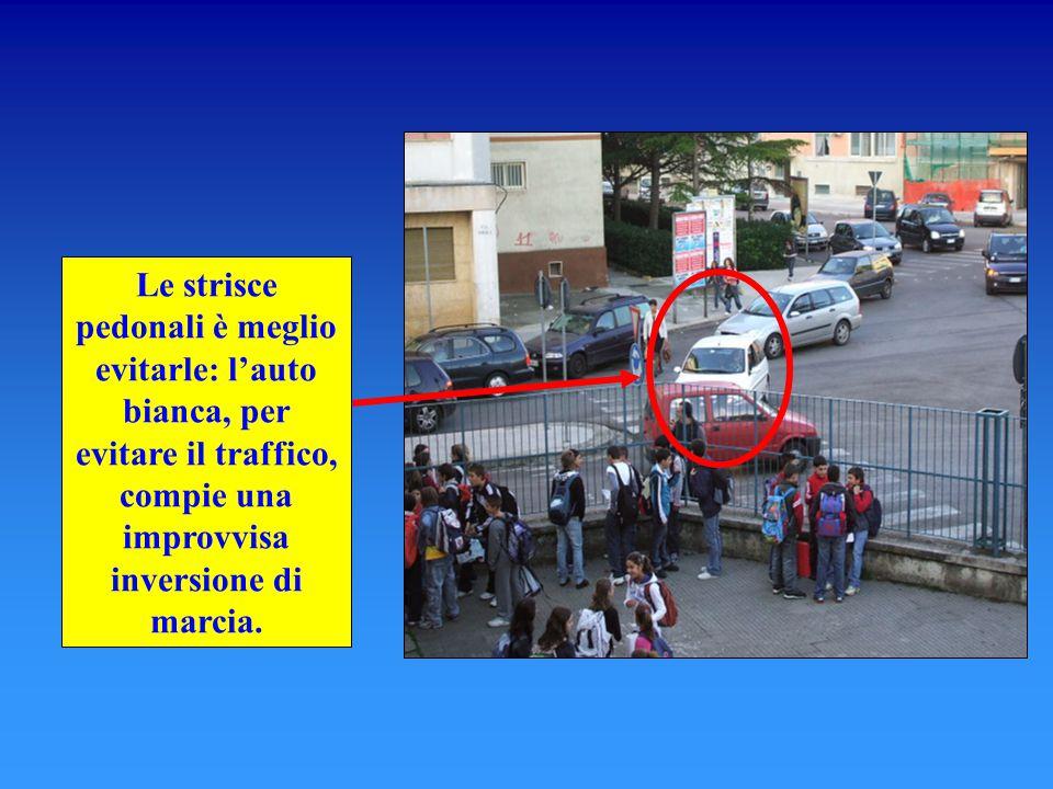 Le strisce pedonali è meglio evitarle: l'auto bianca, per evitare il traffico, compie una improvvisa inversione di marcia.