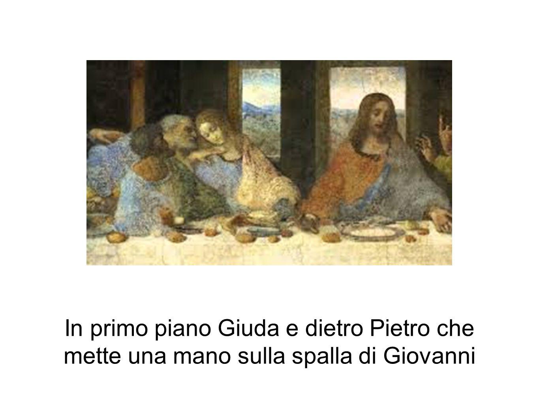 In primo piano Giuda e dietro Pietro che mette una mano sulla spalla di Giovanni