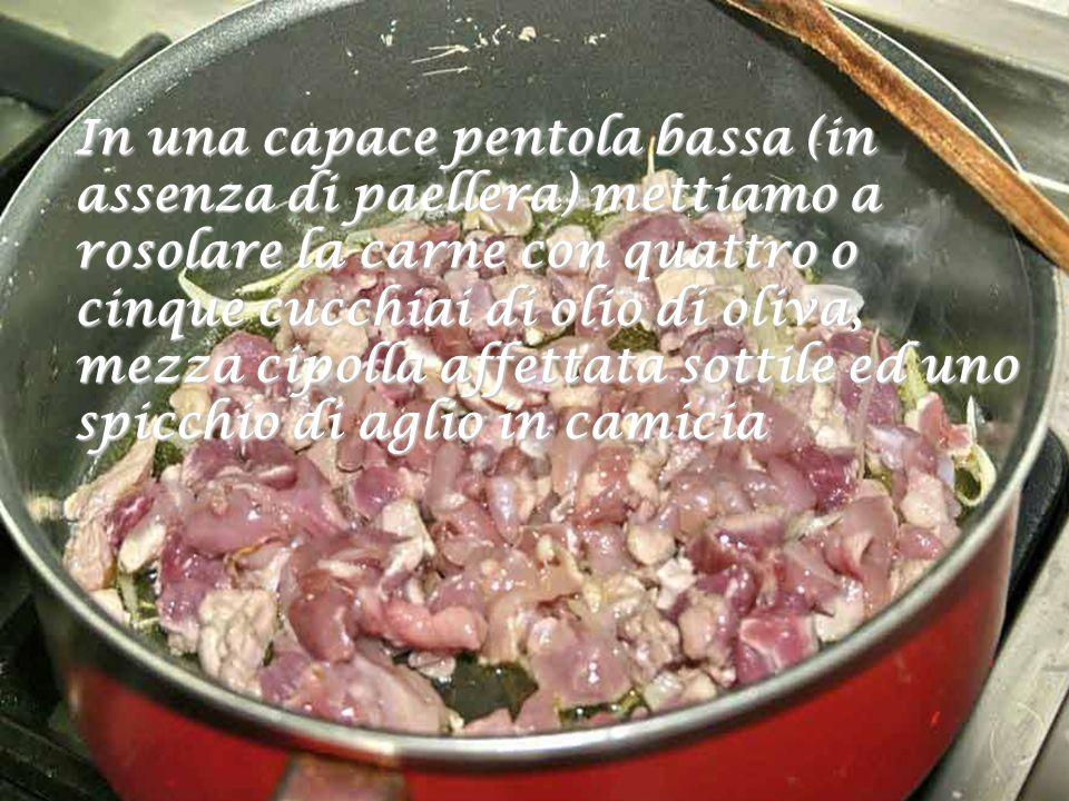 In una capace pentola bassa (in assenza di paellera) mettiamo a rosolare la carne con quattro o cinque cucchiai di olio di oliva, mezza cipolla affettata sottile ed uno spicchio di aglio in camicia