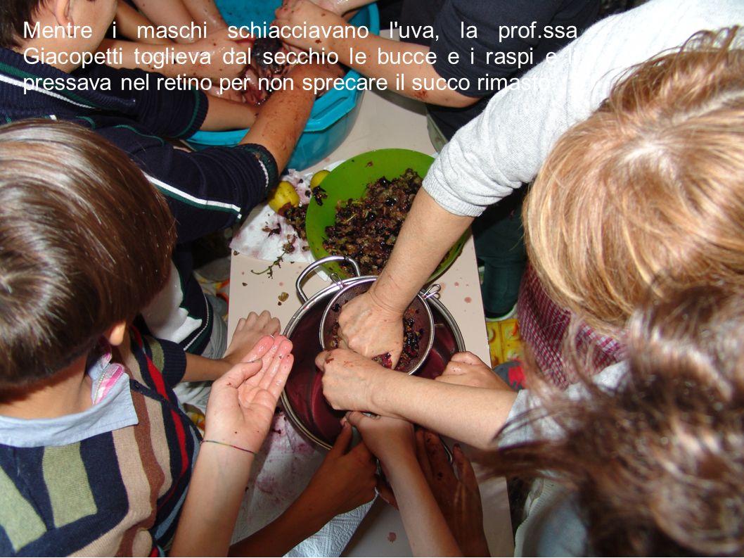 Mentre i maschi schiacciavano l'uva, la prof.ssa Giacopetti toglieva dal secchio le bucce e i raspi e li pressava nel retino per non sprecare il succo