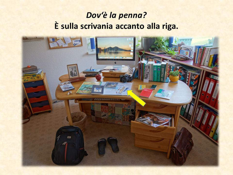 Dov'è la penna? È sulla scrivania accanto alla riga.