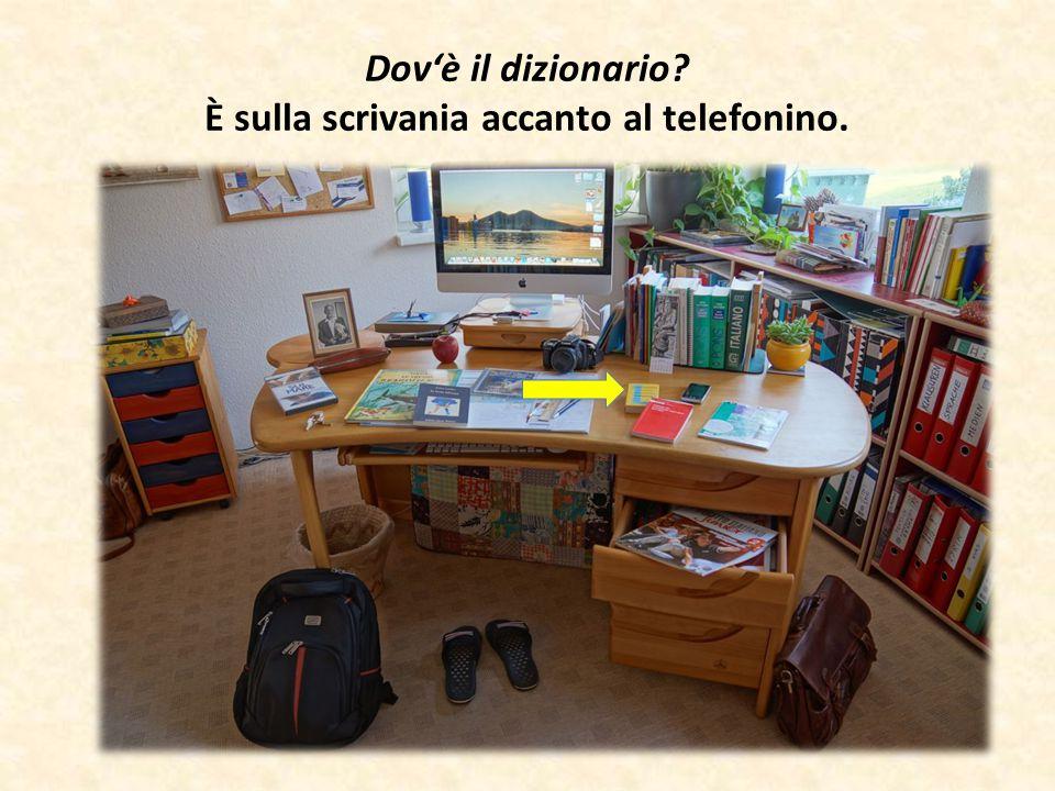 Dov'è il dizionario È sulla scrivania accanto al telefonino.