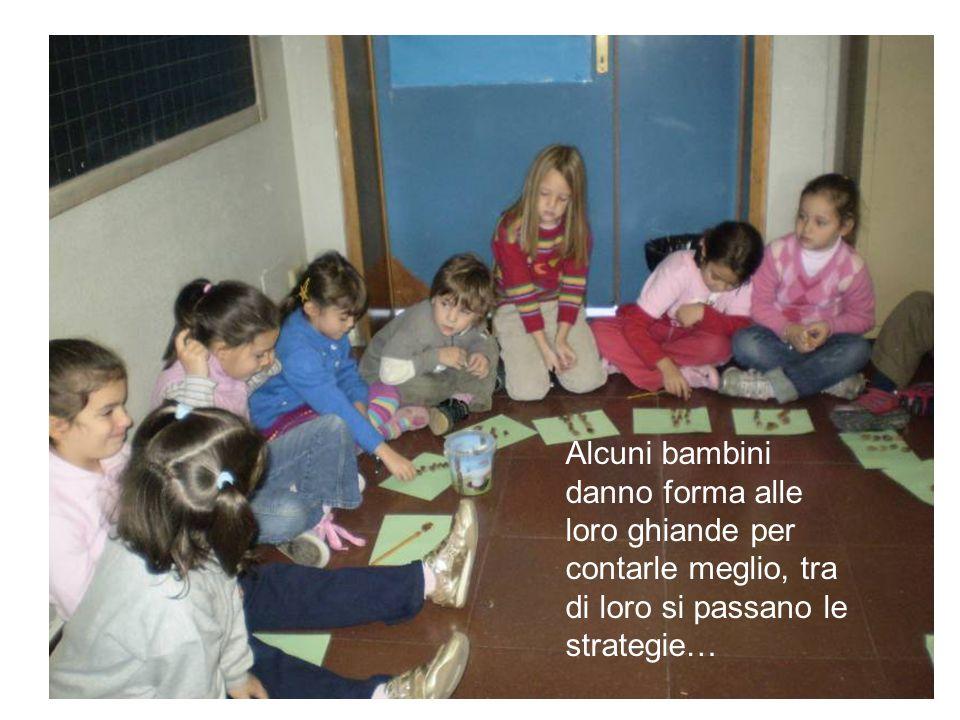 Alcuni bambini danno forma alle loro ghiande per contarle meglio, tra di loro si passano le strategie…