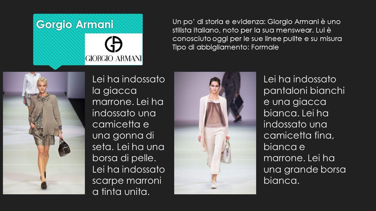 Gorgio Armani Gorgio Armani Lei ha indossato la giacca marrone. Lei ha indossato una camicetta e una gonna di seta. Lei ha una borsa di pelle. Lei ha