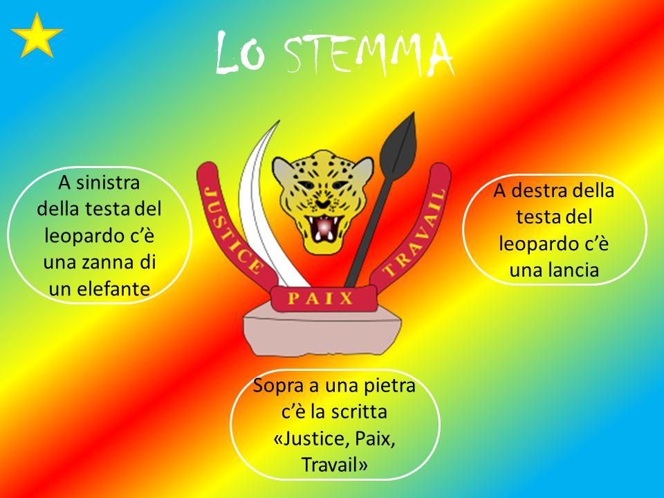 LO STEMMA Sopra a una pietra c'è la scritta «Justice, Paix, Travail» A destra della testa del leopardo c'è una lancia A sinistra della testa del leopardo c'è una zanna di un elefante