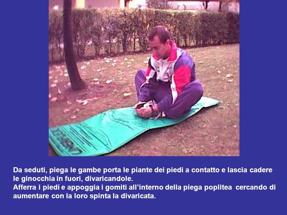 Da seduti, piega le gambe porta le piante dei piedi a contatto e lascia cadere le ginocchia in fuori, divaricandole. Afferra i piedi e appoggia i gomi