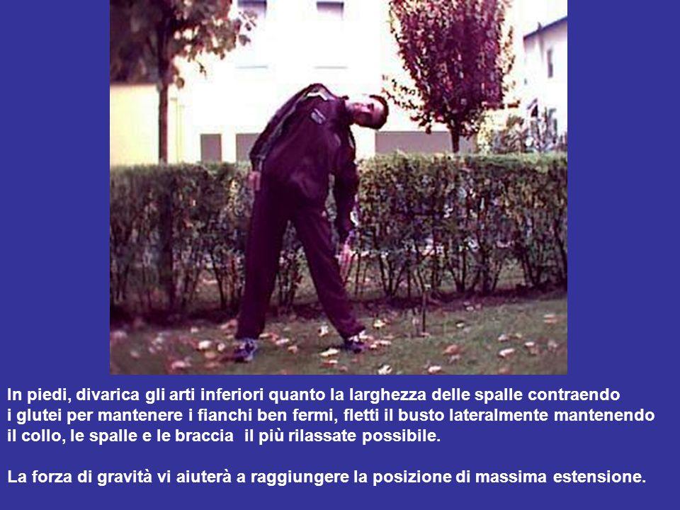 In piedi, divarica gli arti inferiori quanto la larghezza delle spalle contraendo i glutei per mantenere i fianchi ben fermi, fletti il busto lateralm