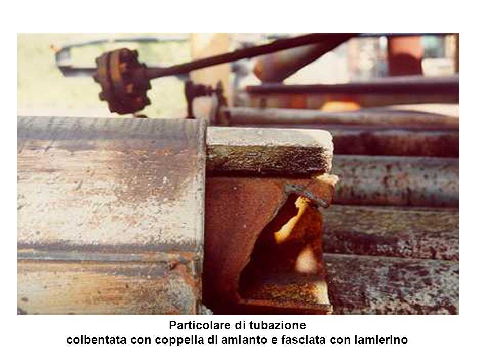 Lavoratore intento alla demolizione degli impianti in prossimità di coibentazioni (coppelle) di amianto non protette.