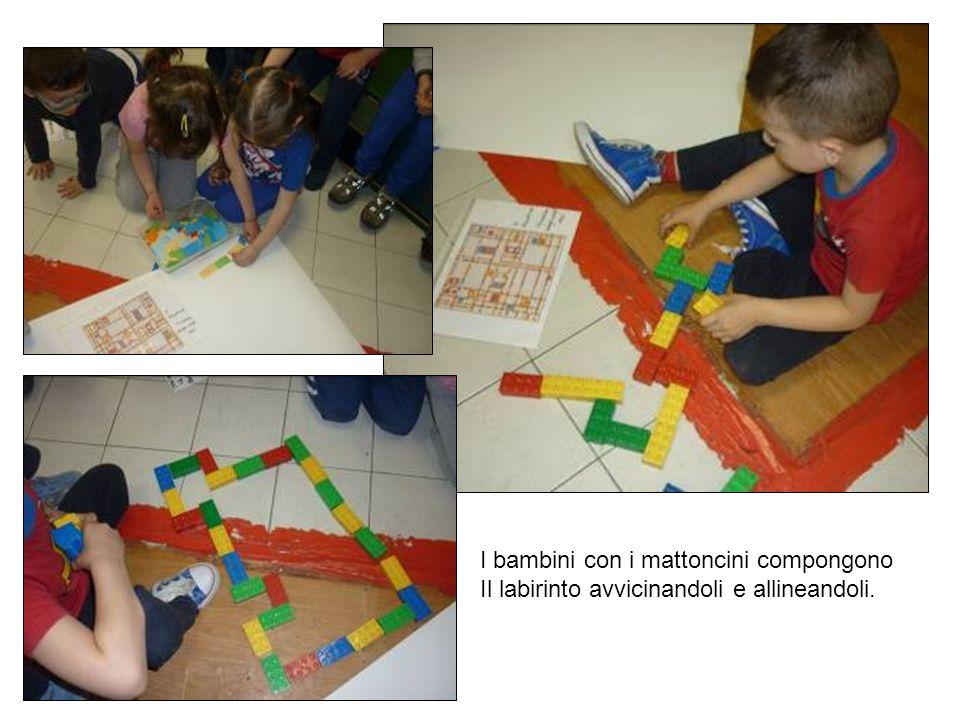 I bambini con i mattoncini compongono Il labirinto avvicinandoli e allineandoli.