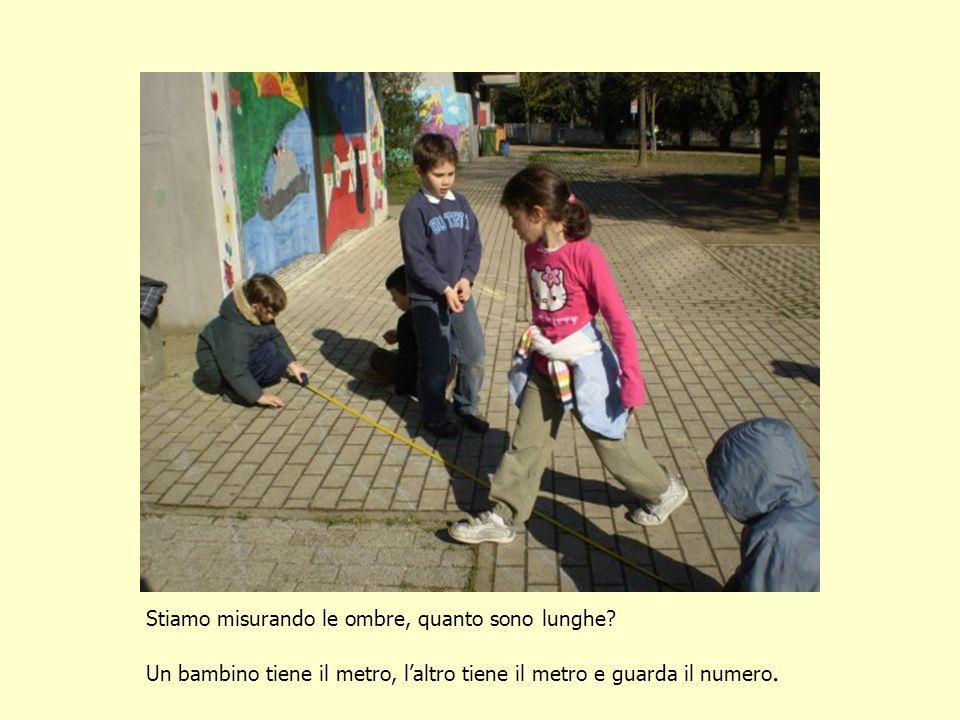 Stiamo misurando le ombre, quanto sono lunghe? Un bambino tiene il metro, laltro tiene il metro e guarda il numero.