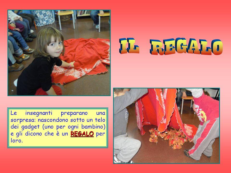 REGALO Le insegnanti preparano una sorpresa: nascondono sotto un telo dei gadget (uno per ogni bambino) e gli dicono che è un REGALO per loro.