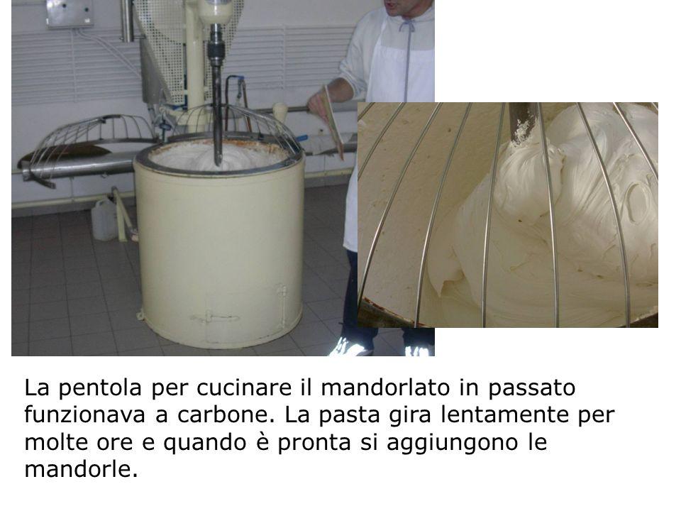 La pentola per cucinare il mandorlato in passato funzionava a carbone. La pasta gira lentamente per molte ore e quando è pronta si aggiungono le mando