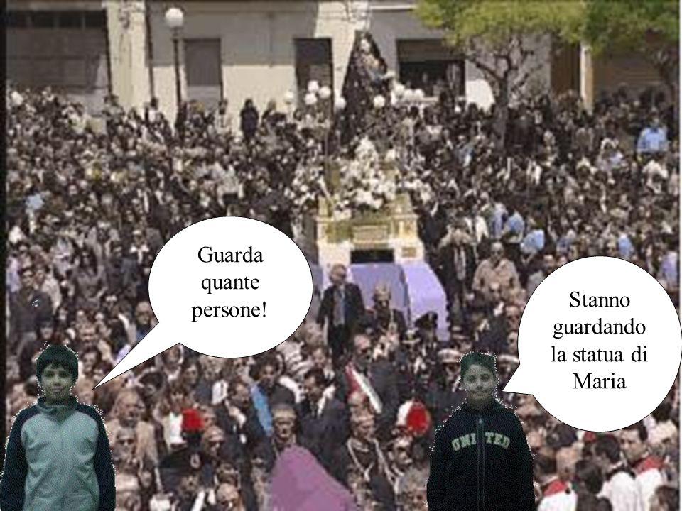 Guarda quante persone! Stanno guardando la statua di Maria
