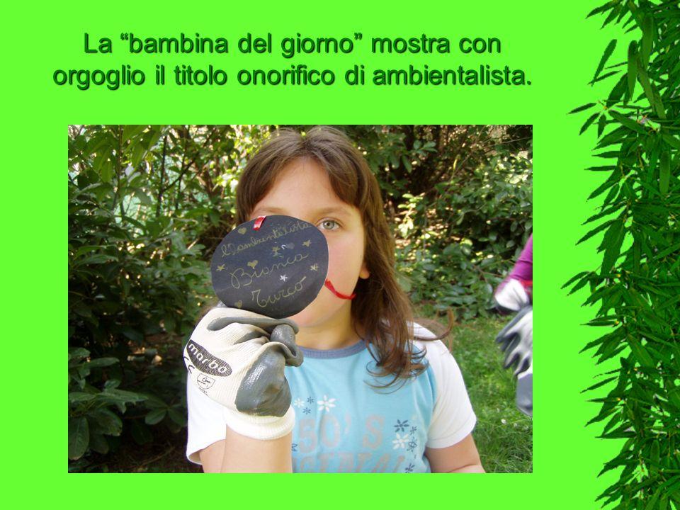 La bambina del giorno mostra con orgoglio il titolo onorifico di ambientalista.