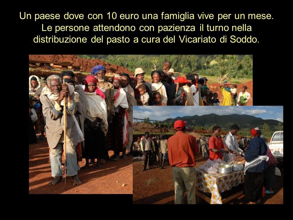 Un paese dove con 10 euro una famiglia vive per un mese. Le persone attendono con pazienza il turno nella distribuzione del pasto a cura del Vicariato