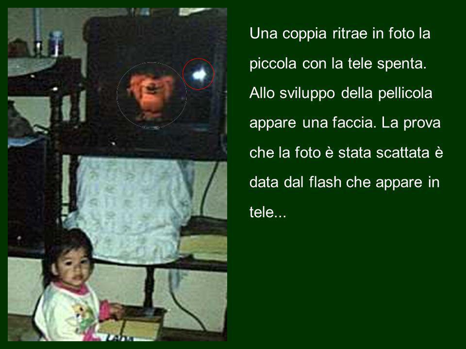 Una coppia ritrae in foto la piccola con la tele spenta.