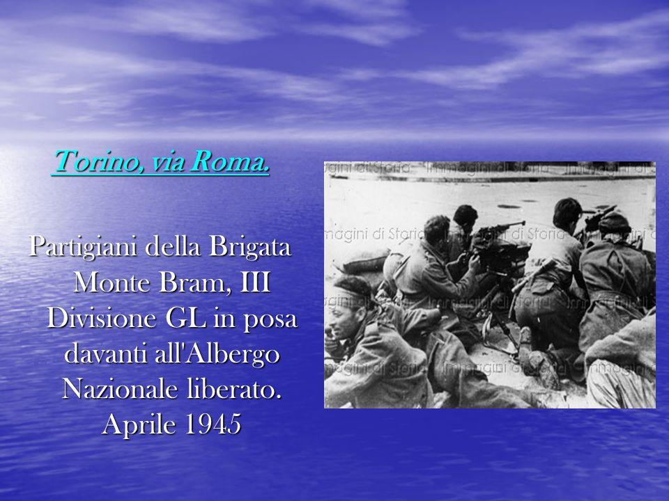 Torino, via Roma. Partigiani della Brigata Monte Bram, III Divisione GL in posa davanti all'Albergo Nazionale liberato. Aprile 1945