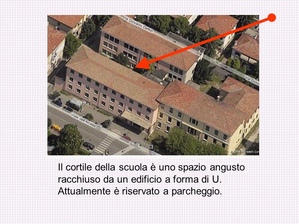 Il cortile della scuola è uno spazio angusto racchiuso da un edificio a forma di U. Attualmente è riservato a parcheggio.