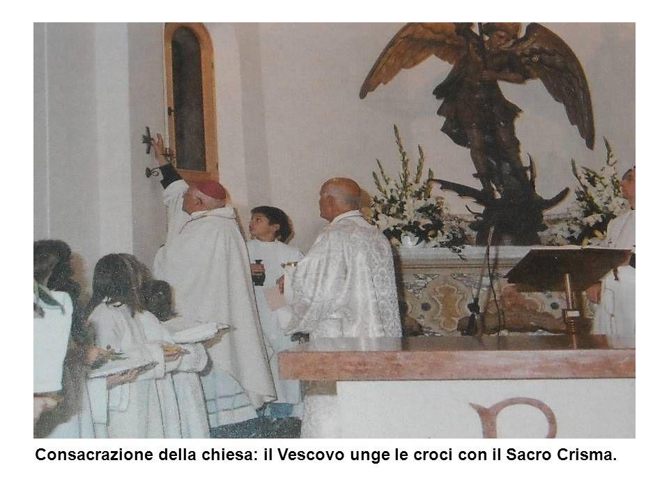 Consacrazione della chiesa: il Vescovo unge le croci con il Sacro Crisma.