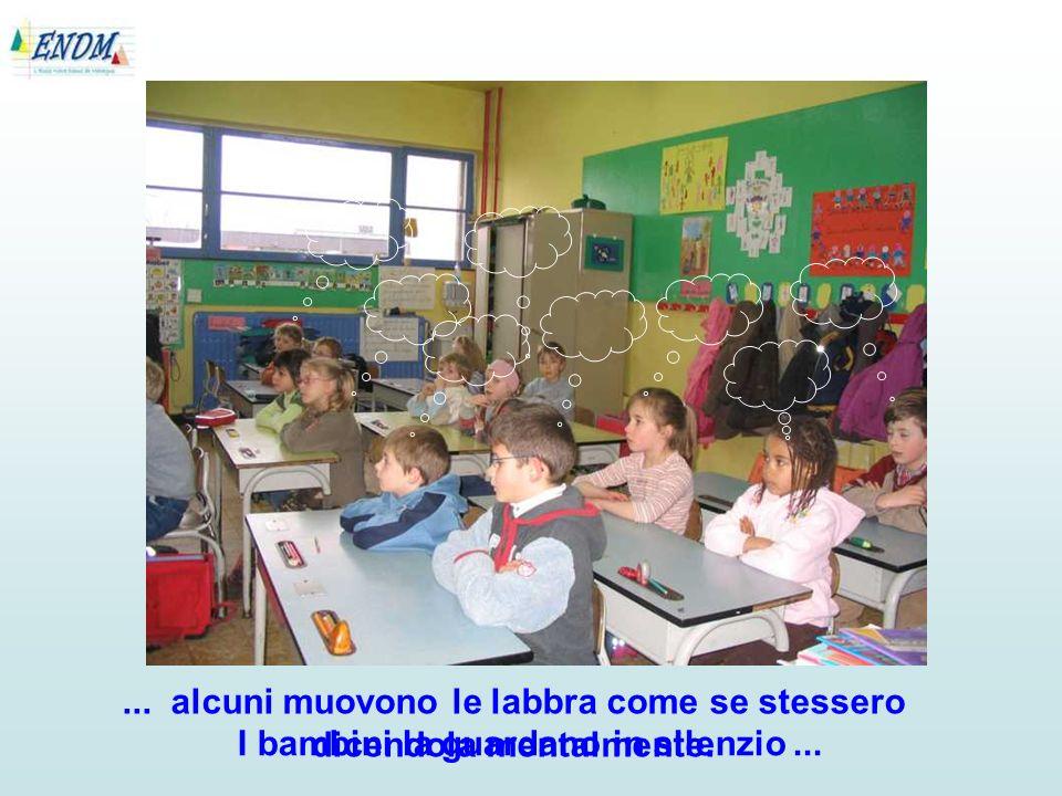 I bambini la guardano in silenzio...... alcuni muovono le labbra come se stessero dicendola mentalmente.