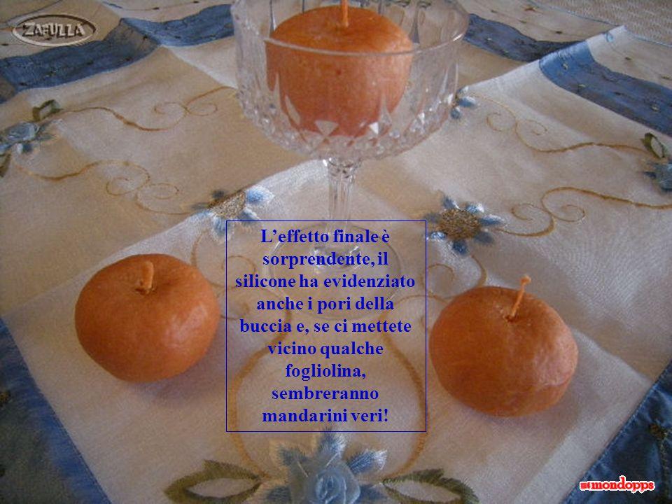 Riempiamo gli stampi di cera calda Dopo qualche ora estraiamo le candele a forma di mandarino Con laiuto di un ferro (anche da calza) scaldato alla fi