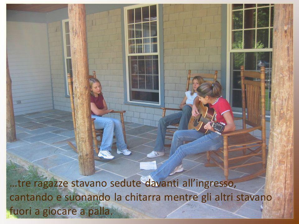 …tre ragazze stavano sedute davanti allingresso, cantando e suonando la chitarra mentre gli altri stavano fuori a giocare a palla.