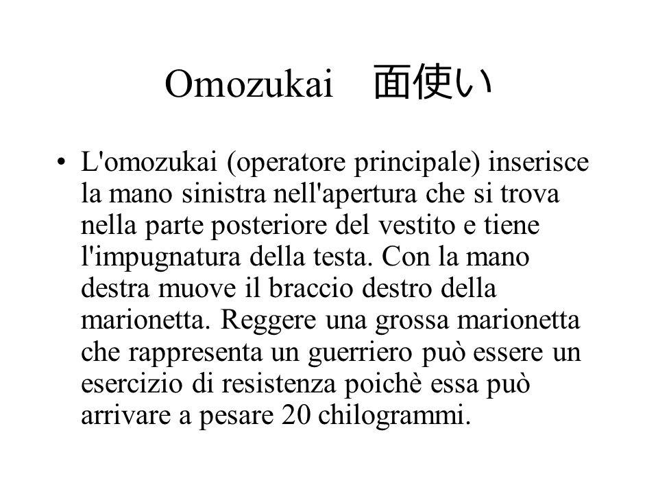 Omozukai L'omozukai (operatore principale) inserisce la mano sinistra nell'apertura che si trova nella parte posteriore del vestito e tiene l'impugnat