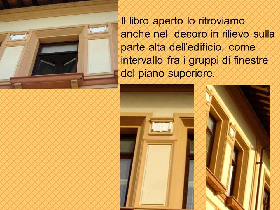 Il libro aperto lo ritroviamo anche nel decoro in rilievo sulla parte alta delledificio, come intervallo fra i gruppi di finestre del piano superiore.