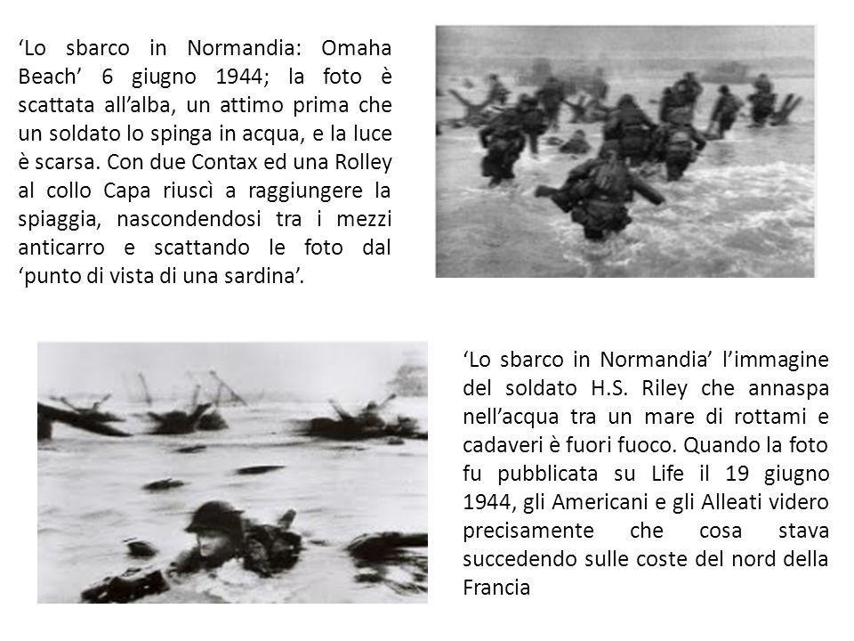 Lo sbarco in Normandia: Omaha Beach 6 giugno 1944; la foto è scattata allalba, un attimo prima che un soldato lo spinga in acqua, e la luce è scarsa.