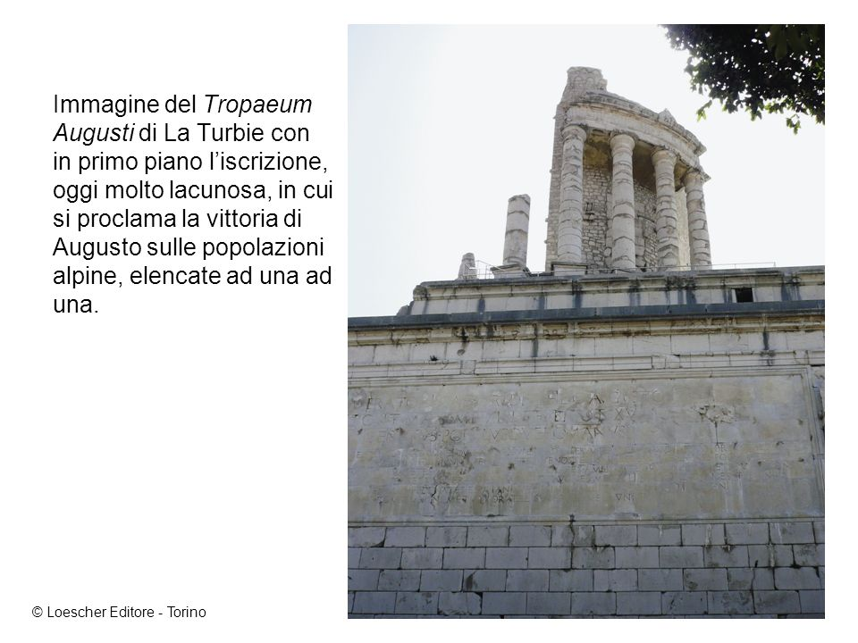 Immagine del Tropaeum Augusti di La Turbie con in primo piano liscrizione, oggi molto lacunosa, in cui si proclama la vittoria di Augusto sulle popolazioni alpine, elencate ad una ad una.