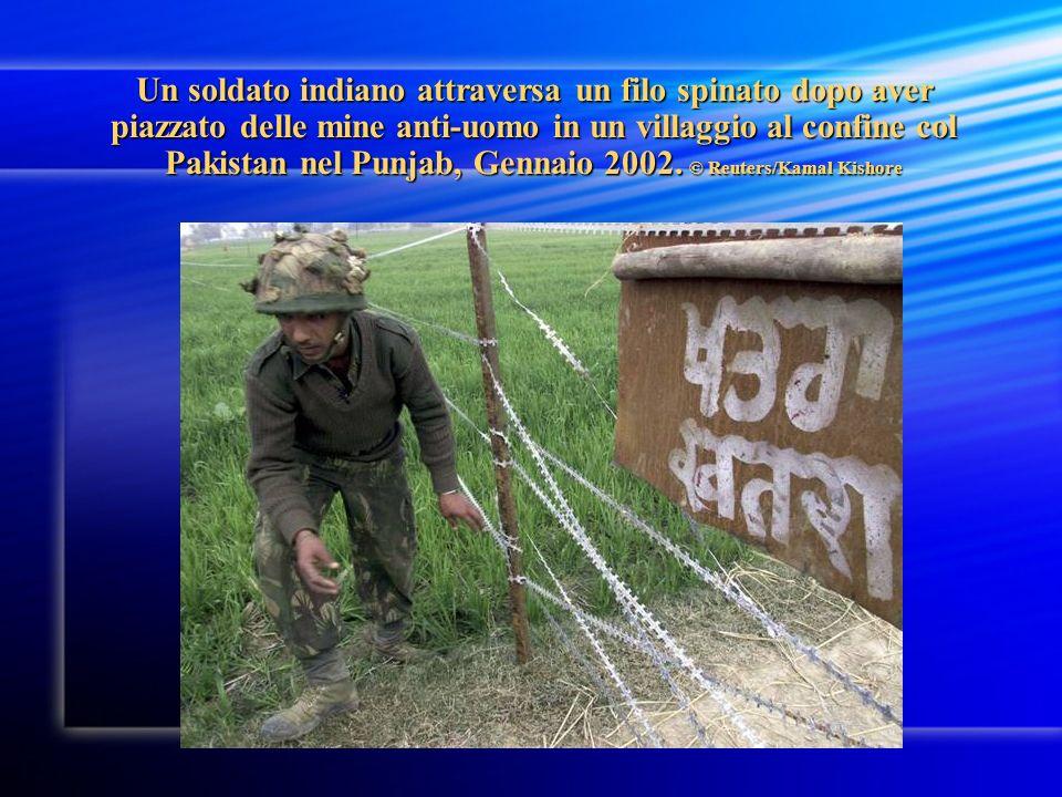 Un soldato indiano attraversa un filo spinato dopo aver piazzato delle mine anti-uomo in un villaggio al confine col Pakistan nel Punjab, Gennaio 2002.