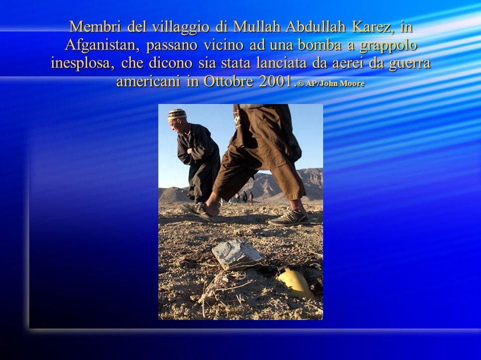 Membri del villaggio di Mullah Abdullah Karez, in Afganistan, passano vicino ad una bomba a grappolo inesplosa, che dicono sia stata lanciata da aerei da guerra americani in Ottobre 2001.