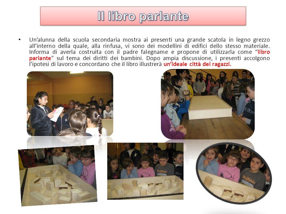 Unalunna della scuola secondaria mostra ai presenti una grande scatola in legno grezzo allinterno della quale, alla rinfusa, vi sono dei modellini di edifici dello stesso materiale.