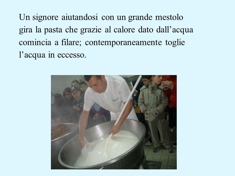 Un signore aiutandosi con un grande mestolo gira la pasta che grazie al calore dato dallacqua comincia a filare; contemporaneamente toglie lacqua in e