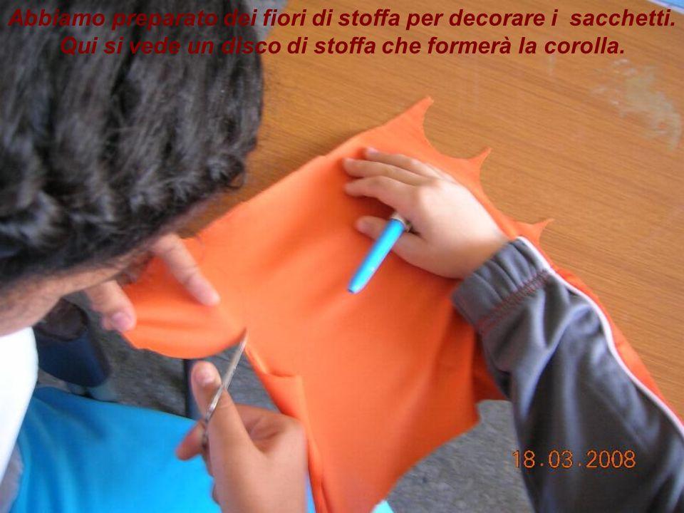 Abbiamo preparato dei fiori di stoffa per decorare i sacchetti. Qui si vede un disco di stoffa che formerà la corolla.