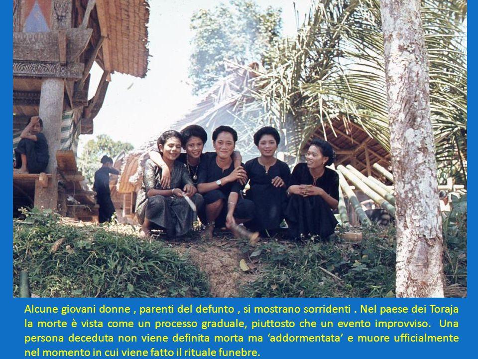 Alcune giovani donne, parenti del defunto, si mostrano sorridenti. Nel paese dei Toraja la morte è vista come un processo graduale, piuttosto che un e