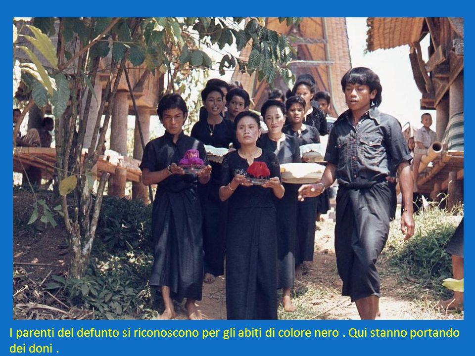 I parenti del defunto si riconoscono per gli abiti di colore nero. Qui stanno portando dei doni.
