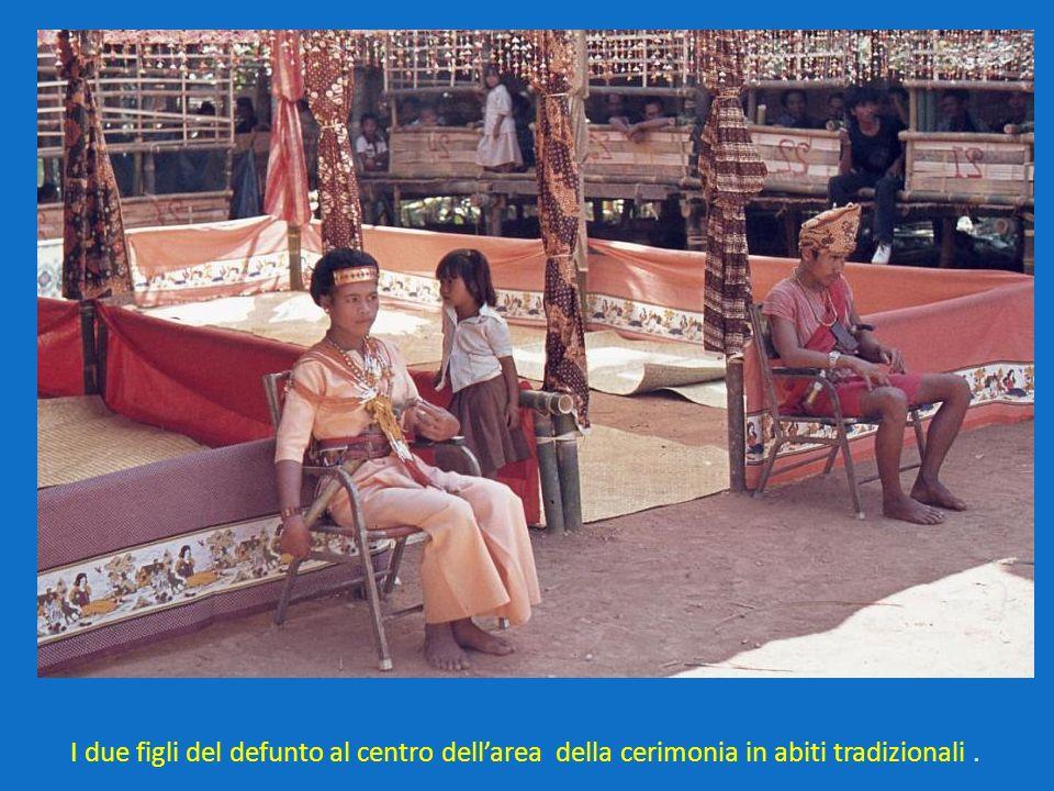 I due figli del defunto al centro dellarea della cerimonia in abiti tradizionali.