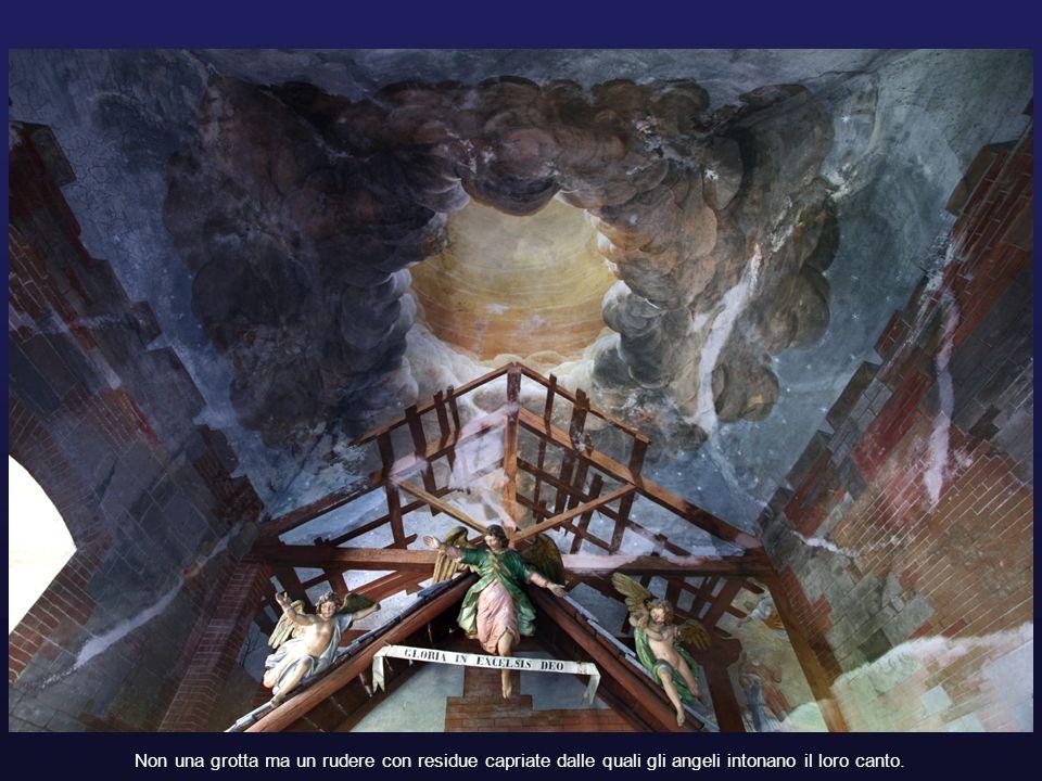 Non una grotta ma un rudere con residue capriate dalle quali gli angeli intonano il loro canto.
