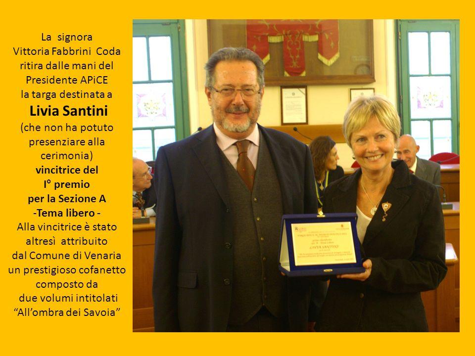 La signora Vittoria Fabbrini Coda ritira dalle mani del Presidente APiCE la targa destinata a Livia Santini (che non ha potuto presenziare alla cerimo
