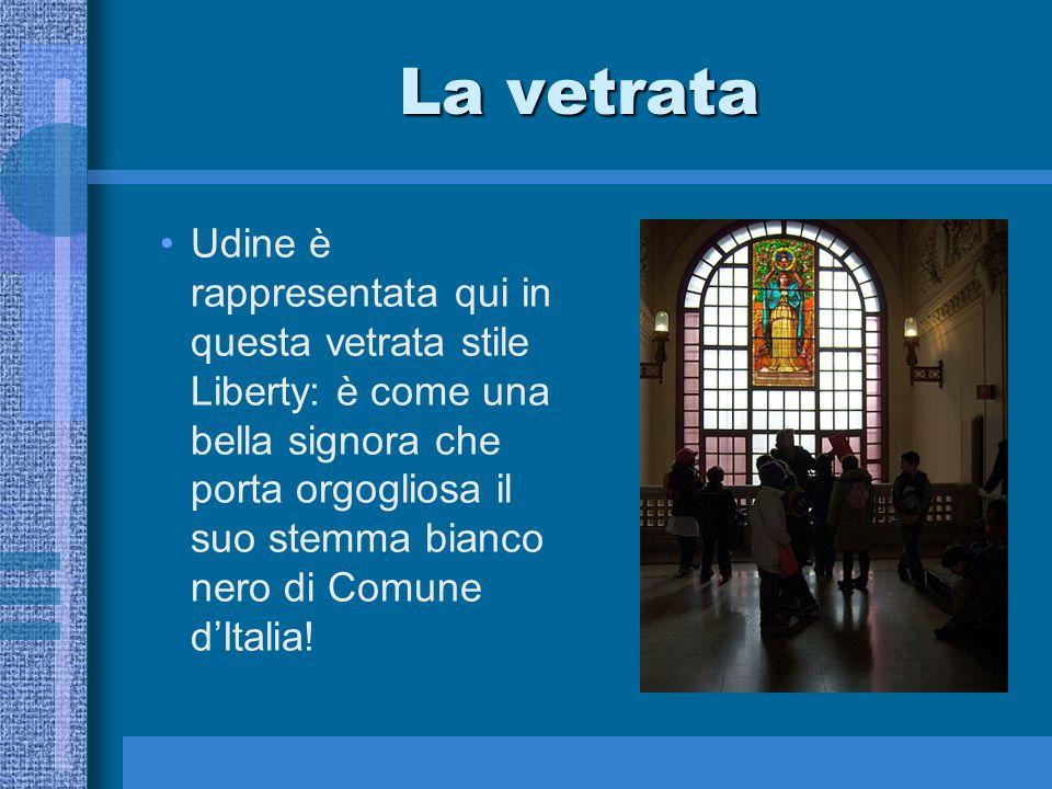 La vetrata Udine è rappresentata qui in questa vetrata stile Liberty: è come una bella signora che porta orgogliosa il suo stemma bianco nero di Comun