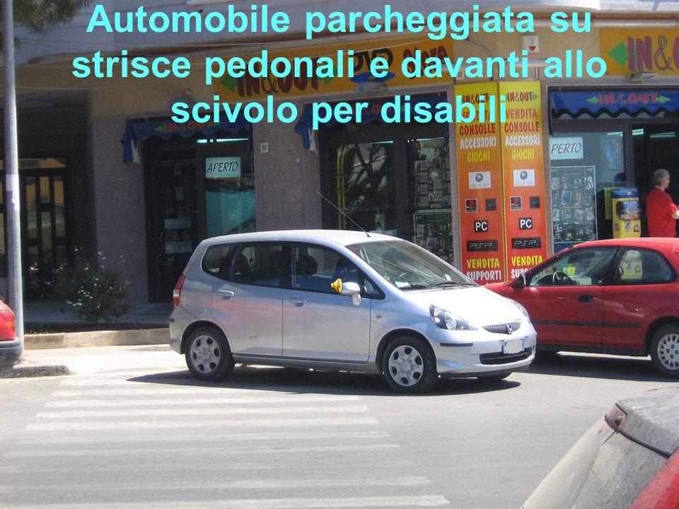 Automobile parcheggiata su strisce pedonali e davanti allo scivolo per disabili